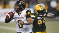Hamilton Tiger-Cats quarterback Jeremiah Masoli (8) gets away from Edmonton Eskimos Jake Ceresna (94) during second half CFL action in Edmonton, Alta., on Friday June 22, 2018. THE CANADIAN PRESS/Jason Franson.