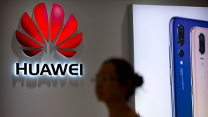 A shopper walks past a Huawei store at a shopping mall in Beijing Wednesday, July 4, 2018. (AP Photo/Mark Schiefelbein)