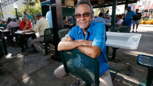 In this Nov. 8, 2017, file photo, Associated Press photographer Alan Diaz poses at Domino Park on Calle Ocho in the Little Havana neighborhood of Miami. Retired Associated Press photojournalist Alan Diaz, whose photo of a terrified 6-year-old Cuban boy named Elian Gonzalez earned him the Pulitzer Prize, died Tuesday, July 3, 2018, his daughter Aillette Rodriguez-Diaz said. He was 71. (AP Photo/Wilfredo Lee, File)
