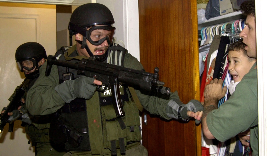 In this April 22, 2000, file photo, by Associated Press photojournalist Alan Diaz, Elian Gonzalez is held in a closet by Donato Dalrymple, one of the two men who rescued the boy from the ocean, right, as government officials search the home of Lazaro Gonzalez for the young boy, in Miami. Retired Associated Press photojournalist Alan Diaz, whose photo of the terrified 6-year-old Cuban boy named earned him the Pulitzer Prize, died Tuesday, July 3, 2018, his daughter Aillette Rodriguez-Diaz said. He was 71. (AP Photo/Alan Diaz, File)
