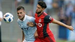 Sporting Kansas City forward Diego Rubio, left, works against Toronto FC midfielder Jonathan Osorio (21) during the first half of an MLS soccer match in Kansas City, Kan., Saturday, July 7, 2018. (AP Photo/Orlin Wagner)