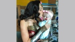 This image released by Kelly Swink Sahady shows Gal Gadot, dressed as Wonder Woman kissing Sahady's daughter Karalyne during a visit to Inova Children's Hospital in Falls Church, Va. Gadot signed autographs and posed for photos with patients and staffers and they posted some of the pictures to social media. (Kelly Swink Sahady via AP)