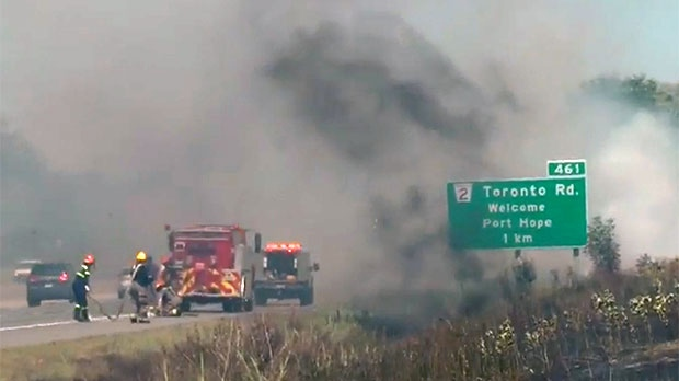Firefighters are seen battling a blaze on Highway 401 in Port Hope.