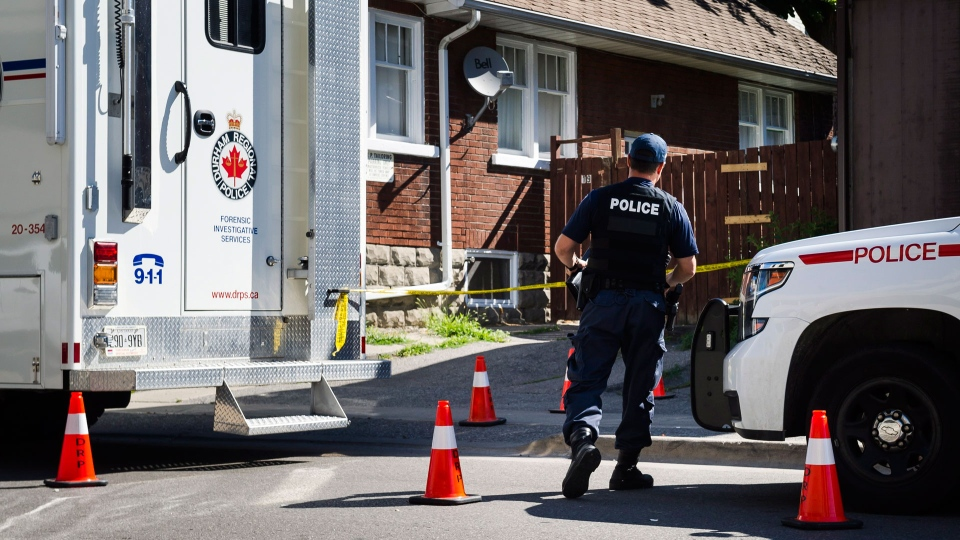 Durham Regional Police enter a home in Oshawa, Ont., on Tuesday, July 10, 2018. THE CANADIAN PRESS/Christopher Katsarov