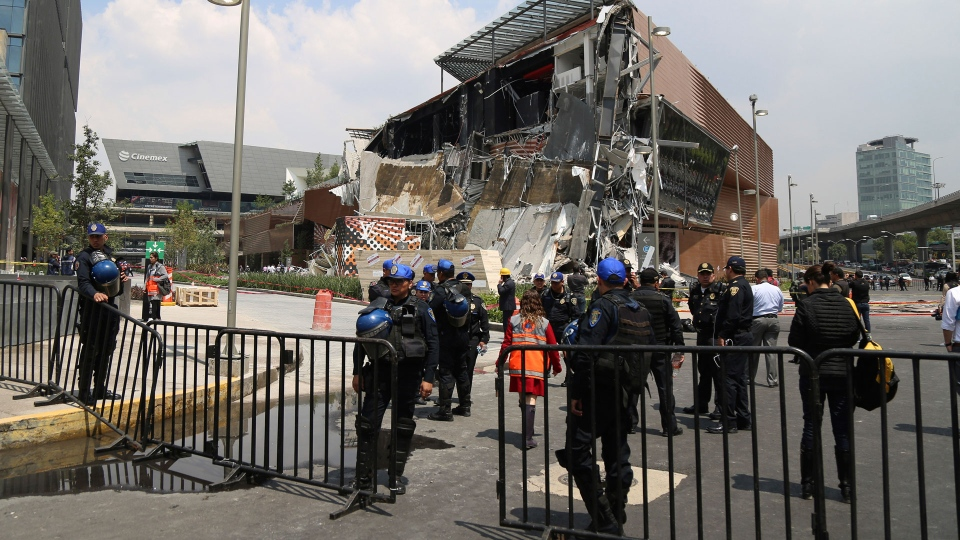 The Artz Pedregal shopping mall stands partially collapsed, on the south side of Mexico City, Thursday, July 12, 2018. The mall collapsed after structural problems apparently led the mall's operators to stage a quick, controlled demolition. The head of civil protection says there were injuries. (AP Photo/Anthony Vazquez)