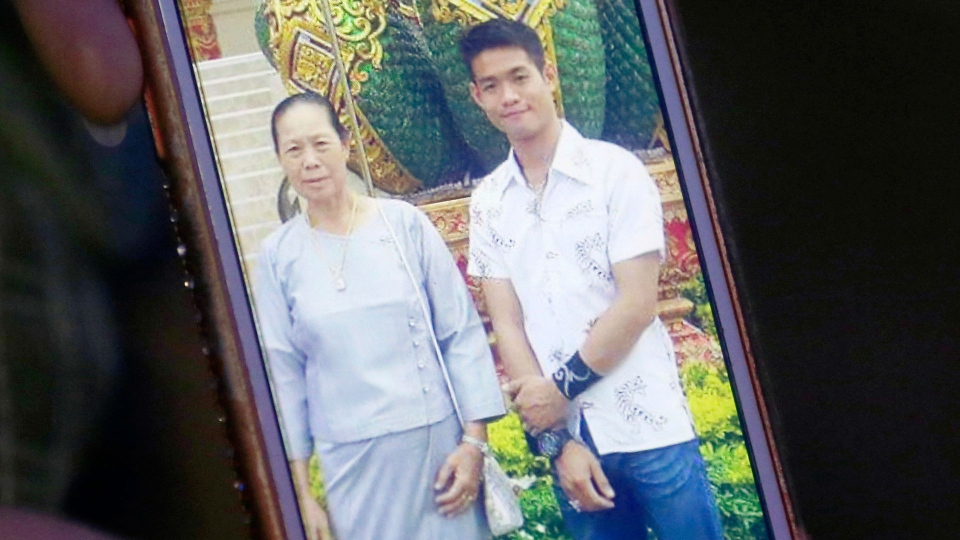 In this July 4, 2018, file photo, the aunt of coach Ekapol Chanthawong shows a picture of the coach and his grandmother on a mobile phone screen, in Mae Sai, Chiang Rai province, in northern Thailand.  (AP Photo/Sakchai Lalit, File)