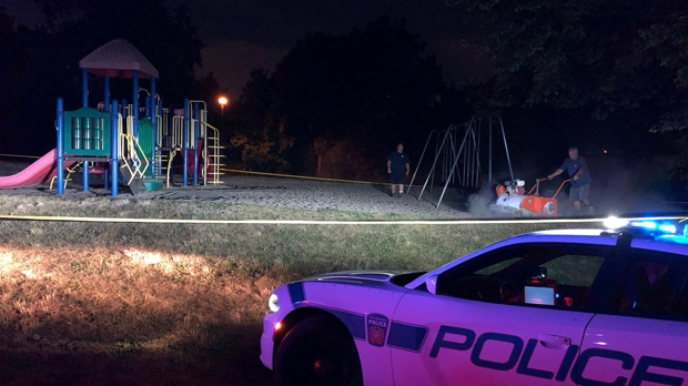 A crew cleans sand at a playground in Mississauga after a boy was poked by a needle he found there on July 13, 2018. (PRP)