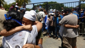 Students, who had taken refuge at the Jesus of Divine Mercy church amid a barrage of armed attacks, embrace relatives, in Managua, Nicaragua, Saturday, July 14, 2018. On Saturday morning, Cardinal Leopoldo Brenes negotiated with the president's office for the safe transfer of students out of the church and to the Metropolitan cathedral. (AP Photo/Alfredo Zuniga)