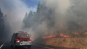 In this Aug. 26, 2013 file photo, a fire truck drives past burning trees as firefighters continue to battle the Rim Fire near Yosemite National Park, Calif. The California Department of Forestry and Fire Protection says a firefighter has been killed while battling a wildfire near Yosemite National Park. Officials say Heavy Fire Equipment Operator Braden Varney was killed Saturday, July 14, 2018, morning while battling the Ferguson Fire. The fire broke out around 10:30 p.m. Friday night in Mariposa County, near the west end of Yosemite National Park and the Sierra National Forest. (AP Photo/Jae C. Hong, File)