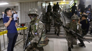 In this Aug. 22, 2017, file photo, South Korean army soldiers conduct an anti-terror drill as part of Ulchi Freedom Guardian exercise inside a subway station in Seoul, South Korea. South Korea has suspended its summertime civil defense drills aimed at preparing against a North Korean attack to keep alive a positive atmosphere for nuclear diplomacy with the North. (AP Photo/Ahn Young-joon, File)