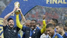 France's Olivier Giroud, left, celebrates with the trophy after the final match between France and Croatia at the 2018 soccer World Cup in the Luzhniki Stadium in Moscow, Russia, Sunday, July 15, 2018. France won the final 4-2. (AP Photo/Matthias Schrader)