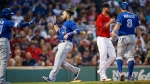 Toronto Blue Jays' Russell Martin, center, celebrates after scoring an a double by by Kevin Pillar that also drove in Kendrys Morales (8) during the third inning of a baseball game in Boston, Friday, July 13, 2018. (AP Photo/Michael Dwyer)