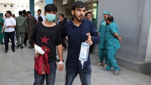 An injured youth is escorted to a hospital following a deadly attack outside the Rural Rehabilitation and Development Ministry in Kabul, Afghanistan, Sunday, July 15, 2018. An Afghan official said several people were killed and others wounded when a suicide bomber detonated his suicide vest in the country's capital. (AP Photo/Rahmat Gul)