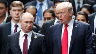 FILE - In this Nov. 11, 2017 file photo, U.S. President Donald Trump and Russia's President Vladimir Putin talk during the family photo session at the APEC Summit in Danang, Vietnam.  (Jorge Silva/Pool Photo via AP, File)