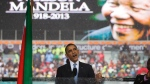 FILE -- In this Tuesday, Dec. 10, 2013, file photo, former U.S. President Barack Obama speaks to crowds attending the memorial service for former South African President Nelson Mandela, background, in Soweto, Johannesburg. In a speech marking the 100th birthday of anti-apartheid leader Nelson Mandela on Tuesday, July 17, 2018, former U.S. President Barack Obama will urge youth around the world to work for human rights and fair societies, highlighting the late South African leader's example of persevering in the struggle for democracy and equal rights for all. (AP Photo/Evan Vucci, File)