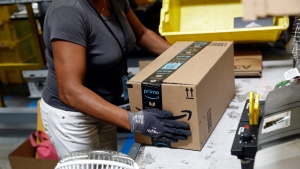FILE- In this Aug. 3, 2017, file photo, Myrtice Harris applies tape to a package before shipment at an Amazon fulfillment center in Baltimore. Amazon's Prime Day starts July 16, 2018, and will be six hours longer than last year's and will launch new products. (AP Photo/Patrick Semansky, File)