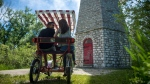 Couple Mehdi Labonne, left, and Monica Kulik take a break from their bike ride at the Gibraltar Point Lighthouse at Toronto Island on Thursday, June 21, 2018. THE CANADIAN PRESS/ Tijana Martin