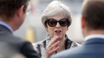 British Prime Minister Theresa May speaks to representatives during a visit to the Airbus area at the Farnborough Airshow in Farnborough, England, Monday, July 16, 2018. (AP Photo/Matt Dunham)