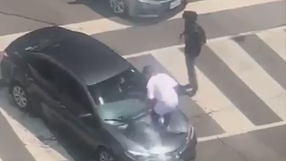 A man stomps on the hood of a vehicle at the intersection of Peter and Richmond streets downtown Monday July 16, 2018. (@JuddSaintJohn /Twitter)