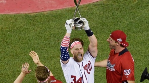 Washington Nationals Bryce Harper holds up the trophy after winning the the Major League Baseball Home Run Derby Monday, July 16, 2018, in Washington. (AP Photo/Susan Walsh)