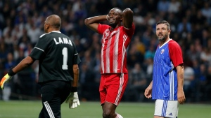 Former Olympic and Jamaican sprinter Usain Bolt, center, reacts during a charity soccer match between members of the 1998 World Cup winning French team and a team of international veteran players who were also involved in the same tournament, at the U Arena in Nanterre, north of Paris, France, Tuesday, June 12, 2018. (AP Photo/Thibault Camus)