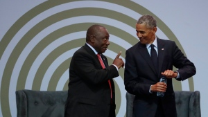 South African President Cyril Ramaphosa, left, and former U.S. President Barack Obama, right, share a light moment at the 16th Annual Nelson Mandela Lecture at the Wanderers Stadium in Johannesburg, South Africa, Tuesday, July 17, 2018. In his highest-profile speech since leaving office, Obama urged people around the world to respect human rights and other values under threat in an address marking the 100th anniversary of anti-apartheid leader Nelson Mandela's birth. (AP Photo/Themba Hadebe)