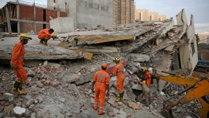 Rescuers search survivors at the site of a collapsed building in Shahberi village, east of New Delhi, India, Wednesday, July 18, 2018. The six-story building under construction collapsed onto an adjacent building. (AP Photo/Altaf Qadri)