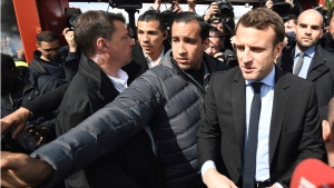 In this Wednesday April 26, 2017 file photo French centrist presidential election candidate Emmanuel Macron, flanked by his bodyguard, Alexandre Benalla, left, arrives in Amiens, northern France.  (Eric Feferberg/Pool via AP, File)