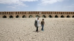 In this Tuesday, July 10, 2018 photo, a woman and a boy walk on the dried up riverbed of the Zayandeh Roud river that no longer runs under the 400-year-old Si-o-seh Pol bridge, named for its 33 arches, in Isfahan, Iran. Farmers in central Iran are increasingly turning to protests, pleading to authorities for a solution as years of drought and government mismanagement of water destroy their livelihoods. (AP Photo/Vahid Salemi)