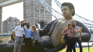 People take photos by a 25ft statue of actor Jeff Goldblum in a pose from a scene in the first Jurassic Park movie, which has been created by a TV channel to celebrate the film's 25th birthday, at Potters Fields Park, London, Wednesday July 18, 2018. Tower Bridge in the background. (Doug Peters/PA via AP)