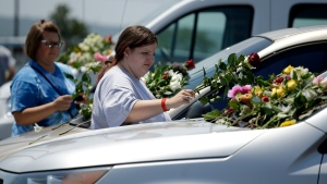 People leave flowers on cars believed to belong to a victims of a last night's duck boat accident, Friday, July 20, 2018 in Branson, Mo. The country-and-western tourist town of Branson, Missouri, mourned Friday for more than a dozen sightseers who were killed when a duck boat capsized and sank in stormy weather in the deadliest such accident in almost two decades. (AP Photo/Charlie Riedel)