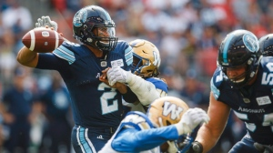 Toronto Argonauts quarterback James Franklin passes under pressure from Winnipeg Blue Bombers' Cory Johnson during the first half of CFL football action in Toronto, Saturday July 21, 2018. THE CANADIAN PRESS/Mark Blinch