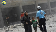 FILE - In this Wednesday, June 14, 2017, file photo, provided by the Syrian Civil Defense group known as the White Helmets, shows civilians rushing out of the damaged buildings after airstrikes hit a school housing a number of displaced people, in the western part of the southern Daraa province of Syria. The Israeli military said Sunday it had rescued members of a Syrian volunteer civil organization, known as White Helmets, from the volatile frontier area and evacuated them to a third country, the first such Israeli intervention in Syria's lengthy civil war. (Syrian Civil Defense White Helmets via AP, File)