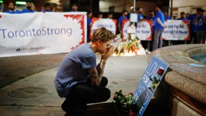 A young man reacts at a vigil remembering the victims of a shooting on Sunday evening on Danforth, Ave. in Toronto on Monday, July 23, 2018. THE CANADIAN PRESS/Mark Blinch