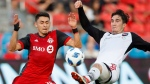 Toronto FC's Marco Delgado battles for the ball with Ottawa Fury FC's Thomas Meilleur-Giguere, right, during the first half of Canadian Championship soccer action in Toronto, Wednesday July 25, 2018. THE CANADIAN PRESS/Mark Blinch