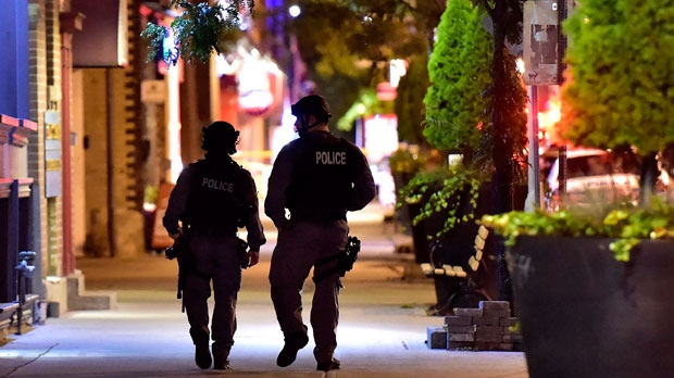 Tactical police officers walk along Danforth Avenue at the scene of a mass casualty incident in Toronto on Sunday, July 22, 2018. THE CANADIAN PRESS/Frank Gunn