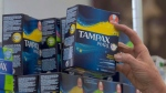 In this June 22, 2016 file photo, a woman restocks tampons at Compton's Market, in Sacramento, Calif. A Halifax university has become the first in the province to offer its students free menstrual products, part of a national movement that has been gaining steam among student leaders. THE CANADIAN PRESS/AP/Rich Pedroncelli