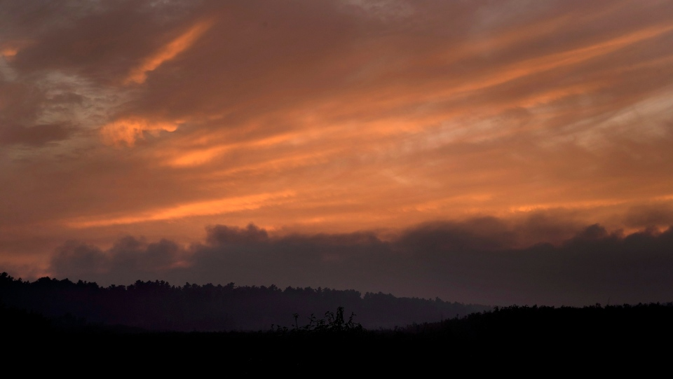 Smoke hangs above the treeline near dusk blocking out the setting sun at forest fires near Killarney, Ontario Tuesday July 31, 2018. (THE CANADIAN PRESS/Fred Thornhill)