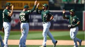 Oakland Athletics' Matt Chapman (26) celebrates the team's 8-3 win over the Toronto Blue Jays with Marcus Semien, second from right, at the end of a baseball game Wednesday, Aug. 1, 2018, in Oakland, Calif. (AP Photo/Ben Margot)