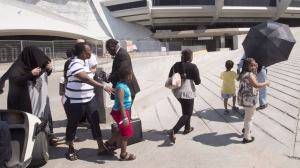 A group of asylum seekers leave Olympic Stadium to go for a walk, in Montreal on Wednesday, August 2, 2017. A long-promised triage system aimed at redirecting irregular border crossers from crowded shelters in Montreal and Toronto will not be in place until as late as the end of September. (Ryan Remiorz / THE CANADIAN PRESS)