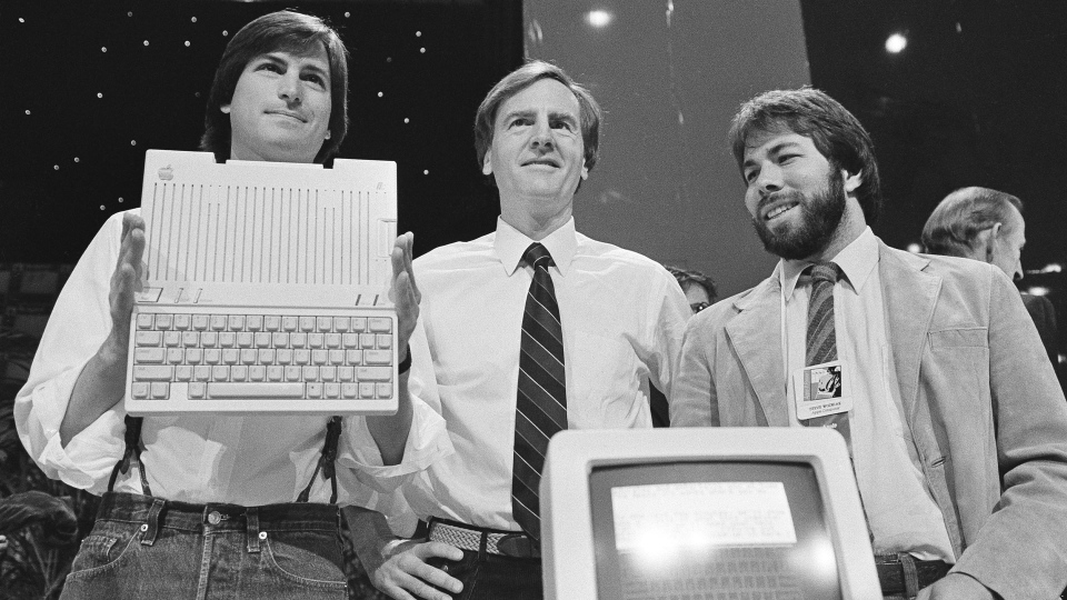 In this April 24, 1984 file photo, Steve Jobs, left, chairman of Apple Computers, John Sculley, center, president and CEO, and Steve Wozniak, co-founder of Apple, unveil the new Apple IIc computer in San Francisco, Calif. (AP Photo/Sal Veder, File)