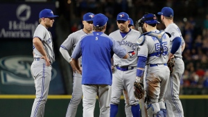 Toronto Blue Jays starting pitcher Marco Estrada, center, is pulled during the eighth inning of the team's baseball game against the Seattle Mariners by manager John Gibbons, front, Saturday, Aug. 4, 2018, in Seattle. (AP Photo/Ted S. Warren)