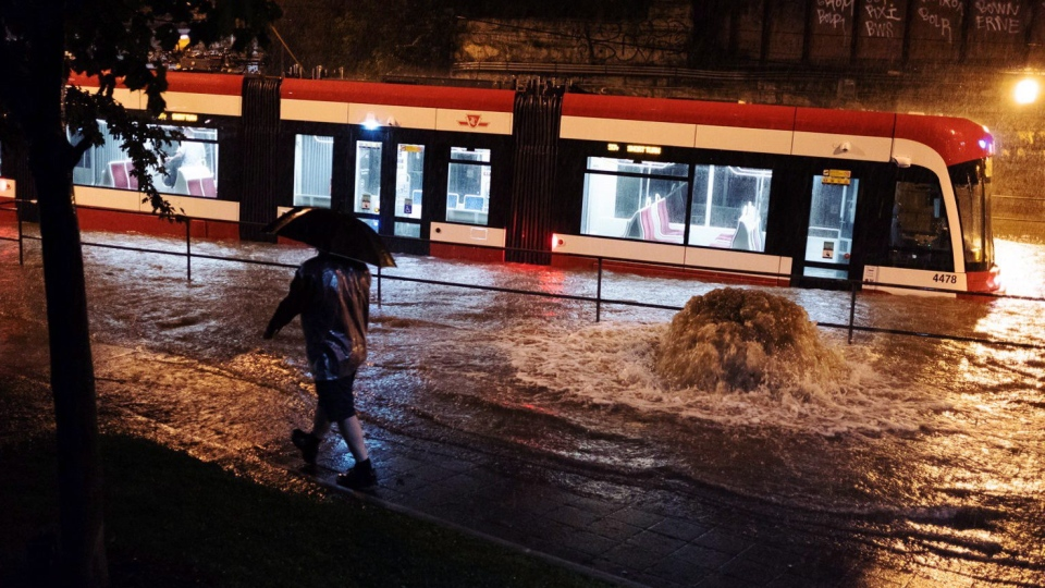 Water overflows from heavy rain, stopping a streetcar on King St. W. in Toronto on Tuesday, August 7, 2018. THE CANADIAN PRESS/Shlomi Amiga