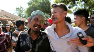 Relatives react as rescue teams recover the bodies of victims killed in an earthquake in North Lombok, Indonesia, Tuesday, Aug. 7, 2018. The north of Lombok was devastated by the powerful quake that struck Sunday night, damaging thousands of buildings and killing a large number of people. Rescuers were still struggling to reach all of the affected areas and authorities expect the death toll to rise. (AP Photo/Tatan Syuflana)