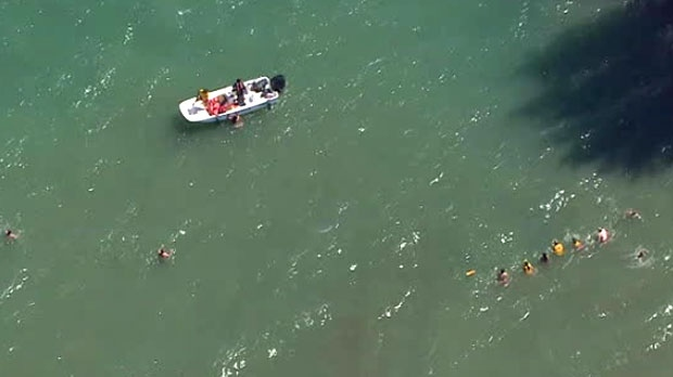 Toronto police are seen working to rescue a swimmer at Woodbine Beach. (Chopper 24)