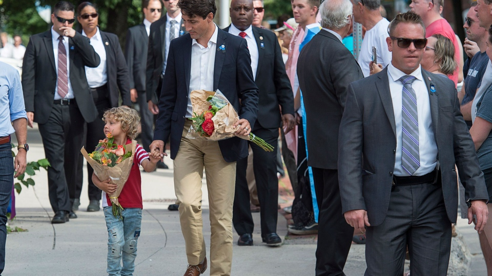 Prime Minister Justin Trudeau, accompanied by his four-year-old son Hadrien, walk to place flowers outside the police station in Fredericton on Sunday, Aug. 12, 2018. Two city police officers were among four people who died in a shooting in a residential area on the city's north side. THE CANADIAN PRESS/Andrew Vaughan