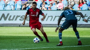 Toronto FC midfielder Jonathan Osorio (21) is challenged by New York City FC defender Sebastien Ibeagha (33) in the second half of MLS soccer action in Toronto on Sunday, August 12, 2018. THE CANADIAN PRESS/Christopher Katsarov
