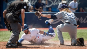 Home plate umpire Ryan Additon watches Toronto Blue Jays' Kevin Pillar slides safely in to home plate as Tampa Bay Rays pitcher Ryne Stanek tries to make the tag in the sixth inning of their American League MLB baseball game in Toronto on Sunday August 12, 2018. THE CANADIAN PRESS/Fred Thornhill