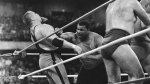 """This April 7, 1986, file photo shows Chicago Bears' William Perry, right, landing a punch on pro wrestler Jim """"The Anvil"""" Neidhart during the """"Over-The-Top-Rope"""" battle royal at Wrestlemania 2 in Rosemont, Ill.  (AP Photo/Charlie Bennett, File"""