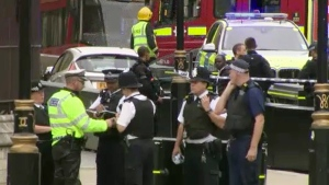 In this frame grab taken Tuesday, Aug. 14, 2018 armed police detain a man, fifth right, who was in a car that crashed into security barriers outside the Houses of Parliament stands to the right of a bus in London. London police say that a car has crashed into barriers outside the Houses of Parliament and that there are a number of injured. (SKY News via AP)